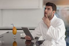 Young freelancer in bathrobe working from home using tablet computer.  Royalty Free Stock Photos