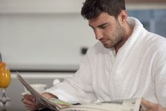 Young freelancer in bathrobe working from home using tablet computer.  Stock Images