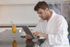 Young freelancer in bathrobe working from home using tablet computer.  Stock Photography