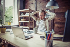 Young freelancer man doing work at home. Man sitting at wooden table with hands on his head royalty free stock images
