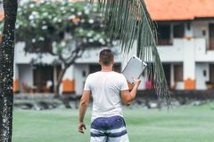 Young freelancer man with laptop in the green tropical park of Bali island. stock photo