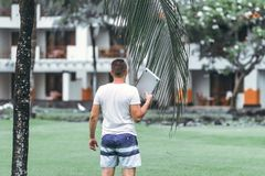 Young freelancer man with laptop in the green tropical park of Bali island. royalty free stock images