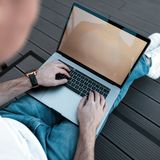 Young freelancer man in stylish jeans works on his laptop indoors. Professional blogger guy sits with a laptop in his lap. Top view of a man`s legs and a royalty free stock image