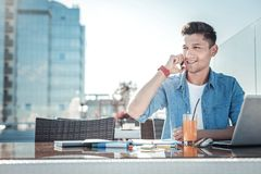 Young freelancer talking on phone while working outdoors. Work is calling. Waist up shot of a happy young man sitting on a terrace of a local cafe and smiling Stock Image