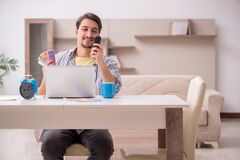 Young male freelancer in time management concept at home