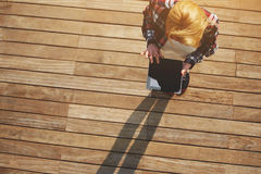 Young freelancer using busy tablet outdoors. Top view blonde hair young woman using digital tablet with with a blank screen standing on wooden floor with copy Stock Photo