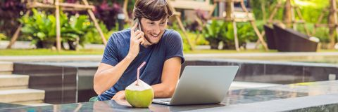 Young freelancer working on vacation next to the swimming pool BANNER, long format stock photography