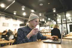 A young freelancer works for a laptop in a lush cafe and drinks coffee. Hipster student at a computer in a cafe. A young freelancer works for a laptop in a lush Stock Photo