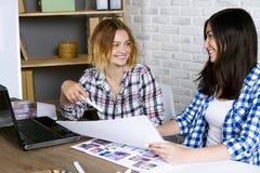 Freelancer interior designer working in design studio. Young freelancers interior designers working develop new appartment project in design studio. Two women stock image
