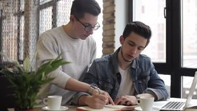 Young freelancers using notebook in the cafe for his work or plans. Young concentrated freelancers using notebook and laptop for their business. Attractive guys stock footage