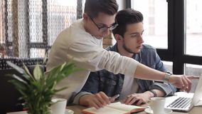 Young freelancers using notebook in the cafe for his work or plans. Young serious freelancers using notebook and laptop for work sitting in the cafe and drinking stock footage