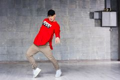 Young freestyle dancer on grey background. Young bold rap dancer in action on grey studio background Stock Photo