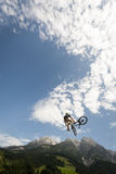 Young freestyler jumps with his bmx high into air Stock Photos