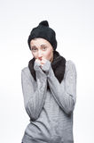 Young freezing girl on gray. Studio portrait of young attractive girl in casual winter clothing which is freezing on gray background royalty free stock photography