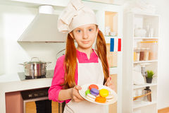 Young French baker with plate of colored macarons Stock Images