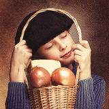 Young French boy wearing black beret is hugging basket with onion and cheese. stock image