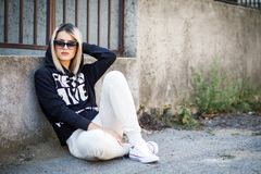 Young fresh cheerful hipster girl sitting on the road in stylish Royalty Free Stock Photography