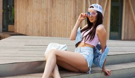 Young fresh cheerful hipster young woman sitting on the steps wearing vintage pink top, jeans shorts and American flag sunglasses. Stock Photography
