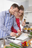 Young fresh married couple in the kitchen cooking together fresh Royalty Free Stock Photo