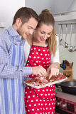 Young fresh married couple in the kitchen eating sausages. Royalty Free Stock Photos