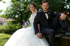 Young fresh married couple sitting on a bench at a park Stock Photography