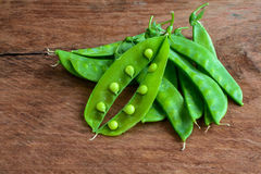 Young fresh pods of green peas on wooden table Royalty Free Stock Photos