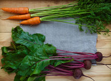 Young freshly picked beets and carrots on a wooden background Stock Photos