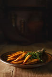 Young fried corn mini with a bundle of thyme. Several fried cobs of young corn with a bunch of thyme on a wooden background in a rustic style. Selective focus royalty free stock photography