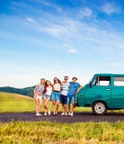 Young frieds with campervan, green nature and blue sky. Young teenage hipster frieds with campervan against green nature and blue sky stock photo