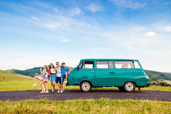 Young frieds with campervan, green nature and blue sky. Young teenage hipster frieds with campervan against green nature and blue sky royalty free stock images