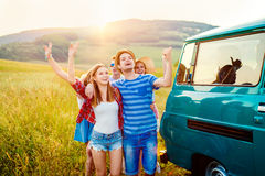 Young frieds with campervan, green nature and blue sky. Young teenage hipster frieds with campervan having fun, against green nature and blue sky, hands up, arms stock images
