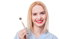 Young, friendly and beautiful dentist woman. Holding usual dental tools Royalty Free Stock Images