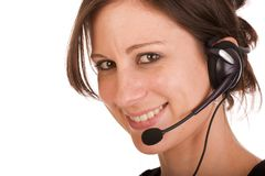 Young friendly brunette woman with headset. Smiling during conversation Stock Photography