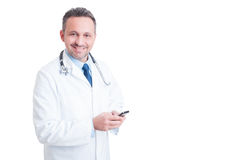 Young and friendly doctor or medic texting on smartphone Royalty Free Stock Images