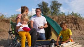Friendly family with children dining out in nature with a tent on a sandy beach stock video footage