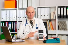 Young friendly family doctor with pocket calculator Stock Images