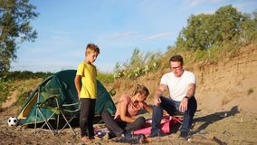 Young family with a child is warming around a fire and tents on nature in summer stock video