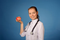Young friendly female doctor with apple Royalty Free Stock Images