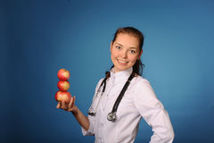 Young friendly female doctor with apples Stock Photo