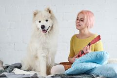 young friendly joyful girl playing the ukulele, the guitar sitting on the couch with her friend a big white dog. stock image