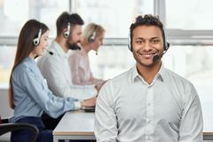 Young friendly male customer service operator. Portrait of a smiling businessman with headsets in a call centre. Bright windows background Royalty Free Stock Image