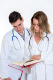 Young friendly medical team with book in lab coat Royalty Free Stock Images