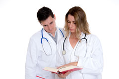 Young friendly medical team with book in lab coat Royalty Free Stock Photos