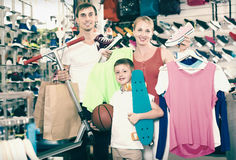 Young friendly parents with boy in sport store. Young friendly parents with boy in school age shopping clothing in sport store. Focus on kid Stock Image