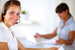 Young friendly receptionist wearing headphone Stock Photos