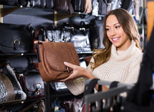 Young friendly woman buying leather purse in shop Stock Photos