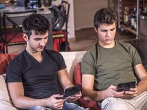 Young friends absorbed with handheld videogames. Two young men in casual chilling on sofa and both playing on handheld video game console Royalty Free Stock Photography