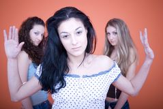Young Friends with Attitude. Group of three teenage females stand apart from each other. Two females in rear looking at the back of the one female in forefront Royalty Free Stock Photo