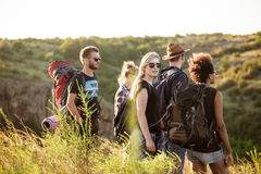 Young friends with backpacks enjoying view, traveling in canyon. Stock Photos