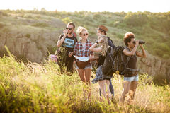 Young friends with backpacks enjoying view, traveling in canyon. Stock Photography